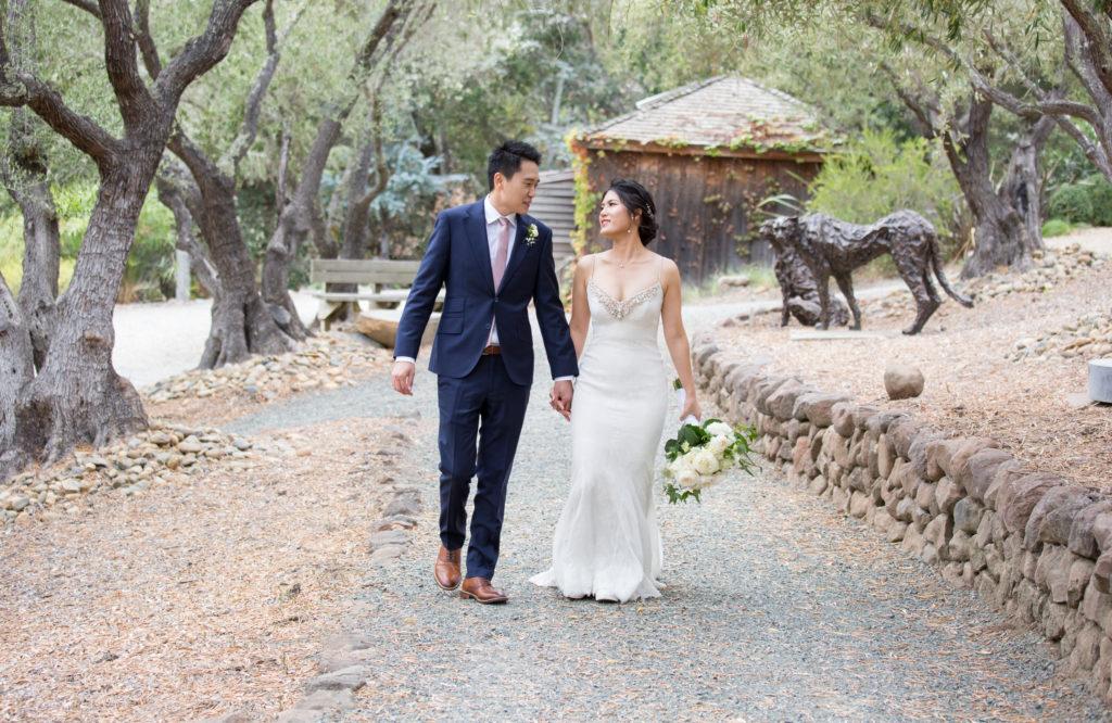 bride and groom walking in Olive Grove in Auberge Du Soleil in Rutherford